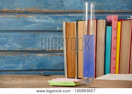 Stack of books, chemical test tube and sticky notes