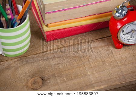 Stack of books, alarm clock and pen holder on wooden background