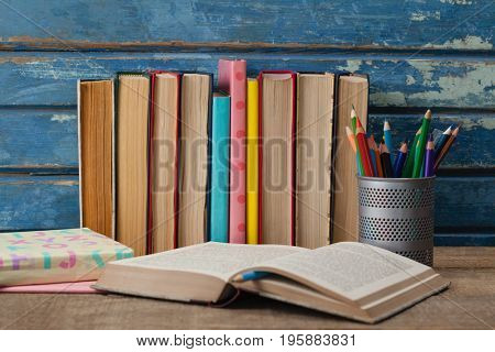 Stack of books, open book and pen holder against blue wooden background
