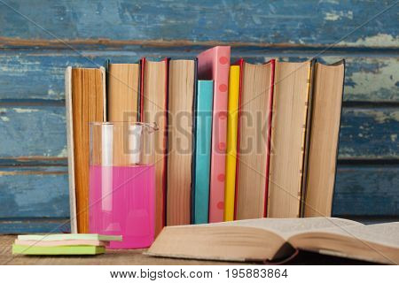 Stack of books, chemical beaker and sticky notes against blue wooden background