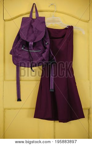 School uniform and bag hanging on yellow door