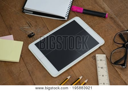 Close-up of school supplies, digital tablet and spectacles on wooden table