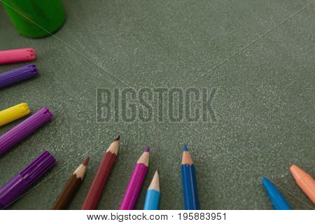 Close-up of various color pencils and marker pens on chalkboard