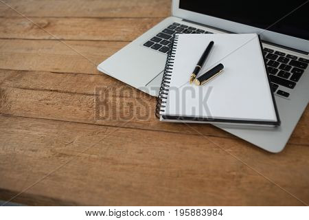 Laptop, pen, and diary on wooden background