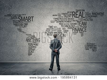 Businessman standing with back and looking at world map on concrete wall
