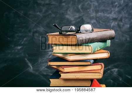 Eye Glasses On Vintage Books Stack - Blackboard Background