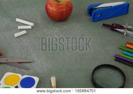 Various school supplies and apple arranged on chalkboard