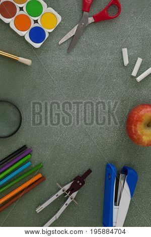 Overhead view of various school supplies and apple arranged on chalkboard