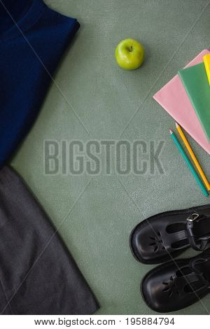 Close-up of school uniform, book, pencil, shoes and apple on chalkboard