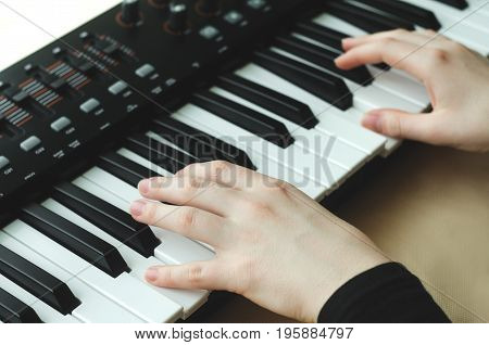 A woman in a black jacket plays a synthesizer. There are two hands in the frame.