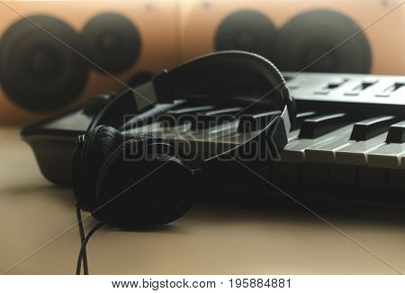 The headphones are on the synthesizer. The synthesizer stands on the background of the speakers. Front view