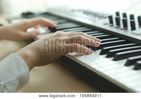 Female hands are dressed in a white shirt are playing on the synthesizer