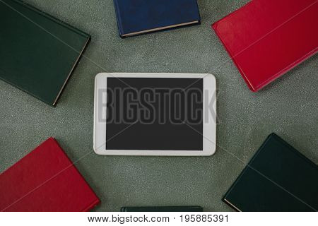 Close-up of digital tablet surrounded with colorful organizers on chalkboard