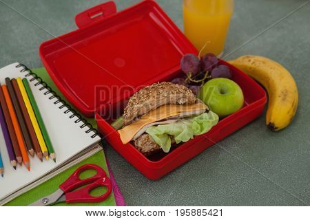Close-up of school supplies and lunch box arranged on chalkboard
