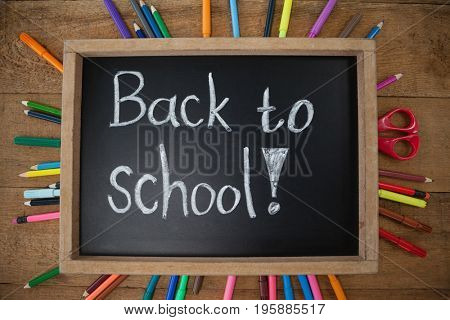 Overhead view of text written on slate surrounded with school supplies
