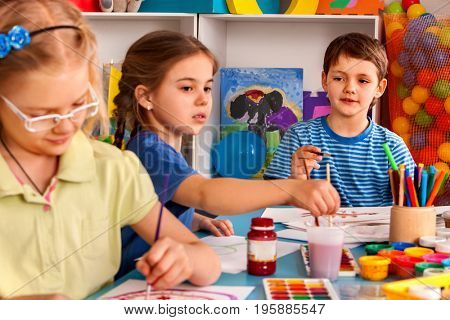 Small students painting in art school class. Children boy and girl drawing by paints on table in kindergarten. Three children are drawing in kindergarten. Girl is upset about something