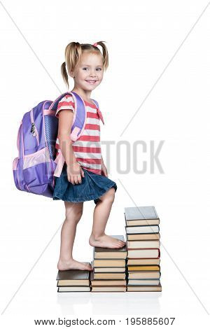 Little beautiful schoolgirl with a backpack on his back climbing up the stairs of books isolated on a white background