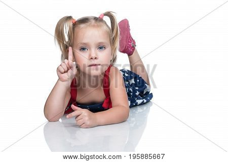 Portrait of a little beautiful girl in a dress lying on the floor with a raised index finger isolated on a white background