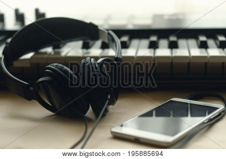 The headphones are connected to the phone lying next to the synthesizer on a beige background. Against the background of the window. Front view