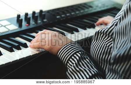A woman in a striped shirt plays a synthesizer. There are two hands in the frame. Side view. Light background