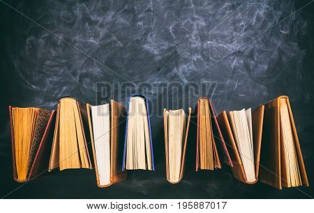 Vintage Books Standing On Blackboard Background - Top View
