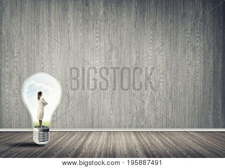 Businesswoman inside of light bulb in empty wood paneled room