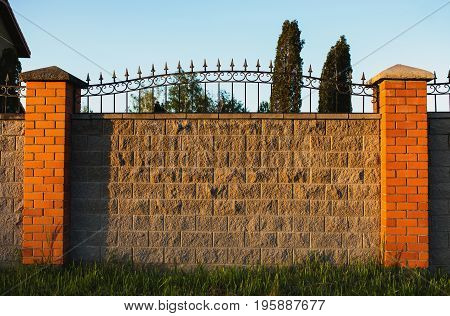 High fence made of gray stone with red brick shutters and forged metal fence. Shutters fence of red brick. High fence of a private house. The sun is shining on the beautiful fence. Brick fence in the evening light