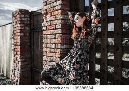 Stylish red-haired girl in a dress and pantyhose in a grid posing outside. Fashion Photo. Beautiful fashion young girl posing. Sexy fashion young woman posing in dress. Attractive fashion thin model posing on fence background. Stylish fashionable dress on