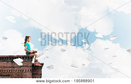 Cute young girl sitting on a building roof and reading a book.