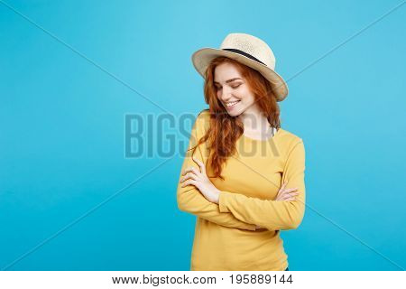 Travel concept - Close up Portrait young beautiful attractive ginger red hair girl with trendy hat and smiling. Blue Pastel Background. Copy space.