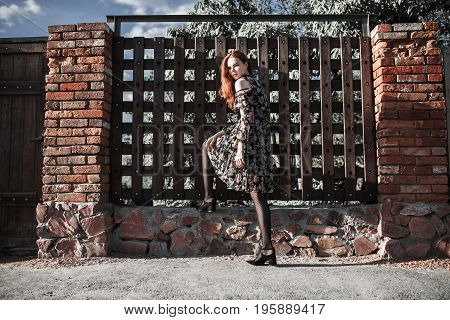 Stylish red-haired girl in a dress and pantyhose in a grid posing outside. Fashion Photo. Beautiful stylish young girl. Sexy stylish young woman. Attractive stylish thin model. Stylish fashionable dress on girl.