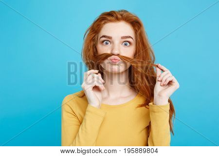 Headshot Portrait of happy ginger red hair girl imitating to be man with hair fake mustache.Pastel blue background. Copy Space.