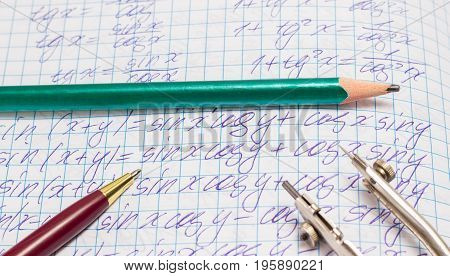School supplies on a sheet of a notebook with mathematical calculations written by hand
