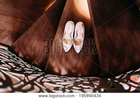 Peach bridal wedding shoes on wooden stairs with decorative railings. Top view