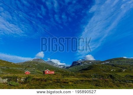 Red wooden cottage in the valley. Stone snowy mountains. Norway.