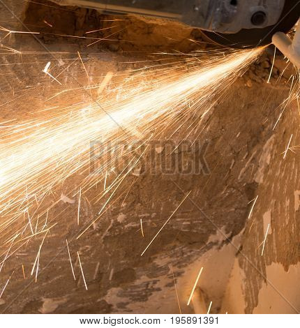Worker cuts a metal pipe at a construction site .