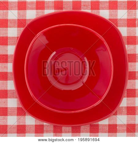 Set Of Stylish Red Plate And A Bowl On White-red Checkered Tablecloth. Top View, Close Up.