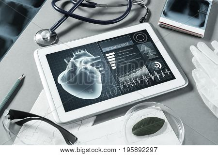 White tablet PC and doctor tools on gray surface.