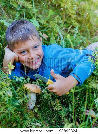 Portrait of cute boy with wild mushroom found in the forest