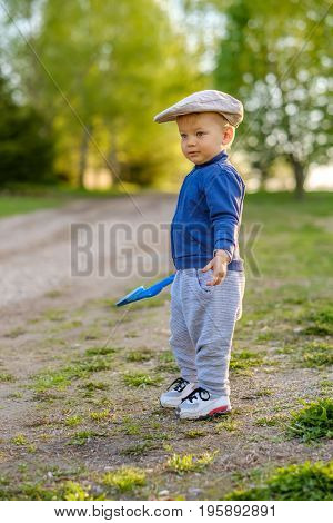 Portrait of toddler child outdoors. Rural scene with one year old baby boy wearing flat cap