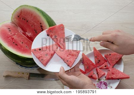 Fresh slices of watermelon on a plate on the wooden table. Organic Ripe Seedless Watermelon Cut into Wedges
