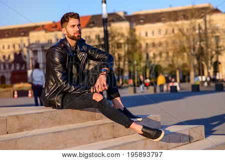 A handsome young hipster man sitting and relaxing on the stairs on a square