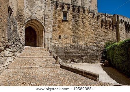 Exit door and stairs of the Palace of the Popes of Avignon, under a sunny blue sky. Located in the Vaucluse department, Provence-Alpes-Côte d'Azur region, southeastern France