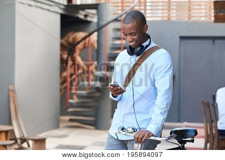 Stylishly dressed young African man reading a text message on his cellphone while standing with his bicycle on a city street