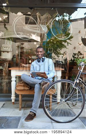 Portrait of a stylish young African man working on a digital tablet while sitting next to his bicycle at a trendy sidewalk cafe