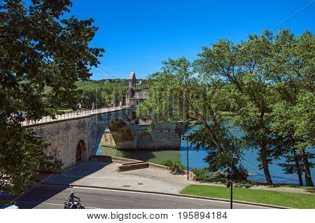 Panoramic view of the Pont d'Avignon (bridge) and the Rhone River under the sunny blue sky, in the city of Avignon. In the Vaucluse department, Provence-Alpes-Côte d'Azur region, southeastern France