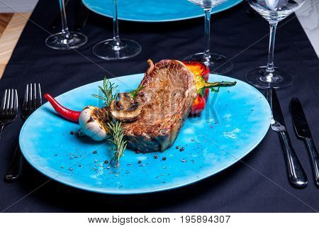 Veal steak with grilled vegetables: mushrooms and peppers on the grill, rosemary and chili