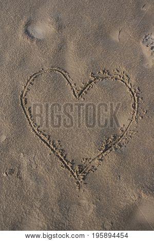 Heart handwritten on the beach sand alphabet