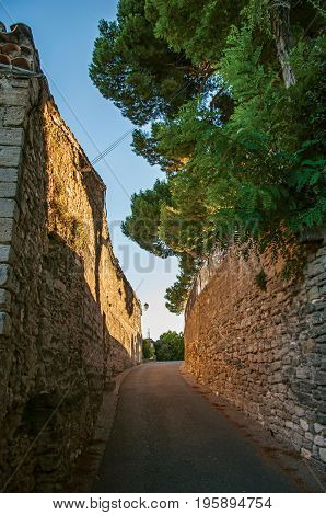 View of traditional stone houses and walls on a street at sunset, in Châteauneuf-de-Gadagne. Located in the Vaucluse department, Provence-Alpes-Côte d'Azur region, southeastern France