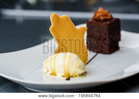 One scoop of the ice cream served on the white plate with brownie and buscuit